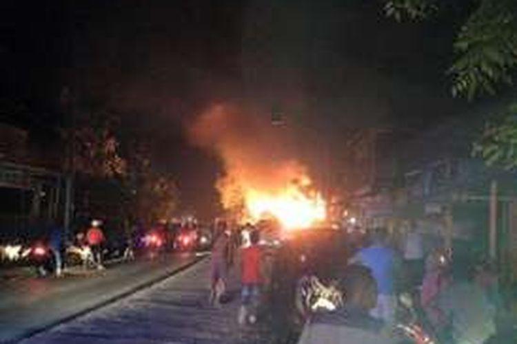 Warga melihat 6 rumah toko (Ruko) milik Said Zulhilmi di lintas nasional Medan – Banda Aceh, Desa Cot Plieng, Kecamatan Syamtalira Bayu, Aceh Utara, yang terbakar, Selasa (26/4/2016) dinihari
