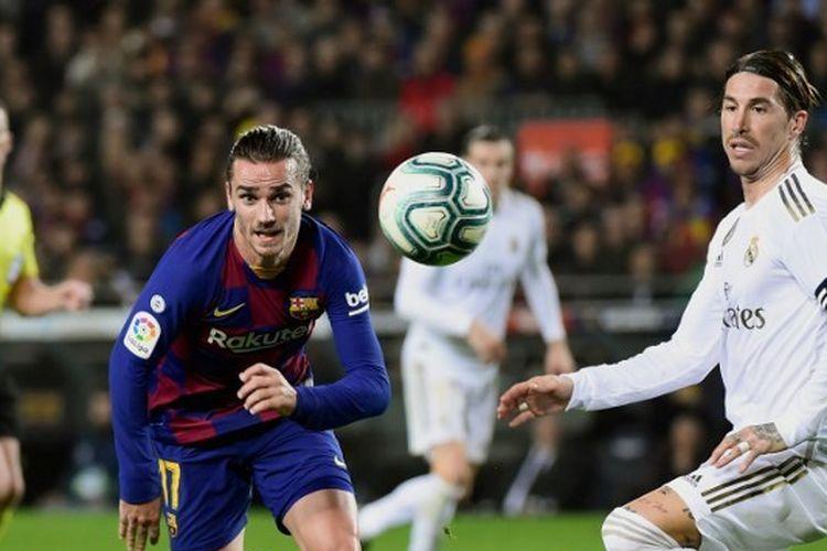 Antoine Griezmann (kiri) dan Segio Ramos (kanan) berusaha mengejar bola dalam laga El Clasico Barcelona vs Real Madrid di Stadion Camp Nou, Rabu (18/12/2019) atau Kamis dini hari WIB