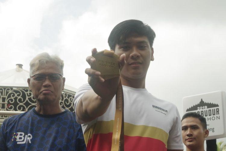 Direktur Utama Bank Jateng, Supriyatno (kiri) menyerahkan medali emas Borobudur Marathon 2019 yang diperkenalkan pada Minggu (6/10/2019)