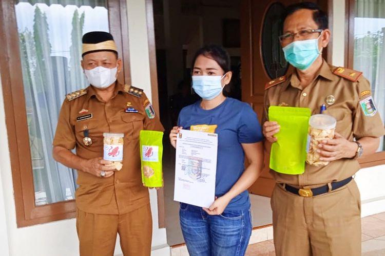 Bupati Lampung Timur Dawam Rahardjo saat menyerahkan sertifikat Perizinan Industri Rumah Tangga (PIRT) kepada salah seorang pelaku UMKM Siska Linda (23) di Rumah Dinas Bupati Lampung Timur pada Selasa (8/6/2021).