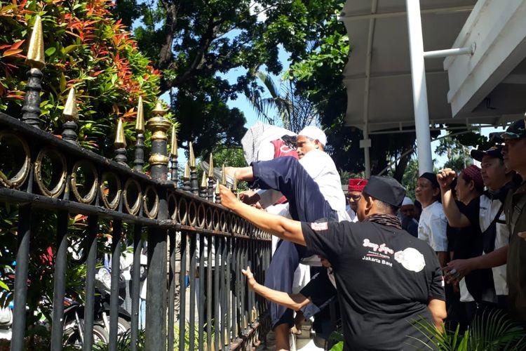 Massa pro-Gubernur DKI Jakarta Anies Baswedan memanjat pagar saat berdemo di Balai Kota DKI Jakarta, Selasa (14/1/2020).