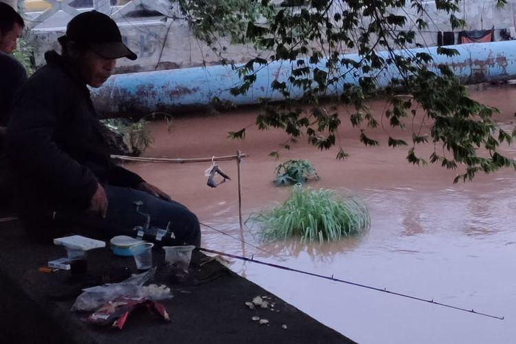 Warga memanfaatkan banjir di Jakarta untuk memancing di Kali Pesanggrahan, Rabu (1/1/2020), karena bisa lebih banyak mendapatkan ikan.