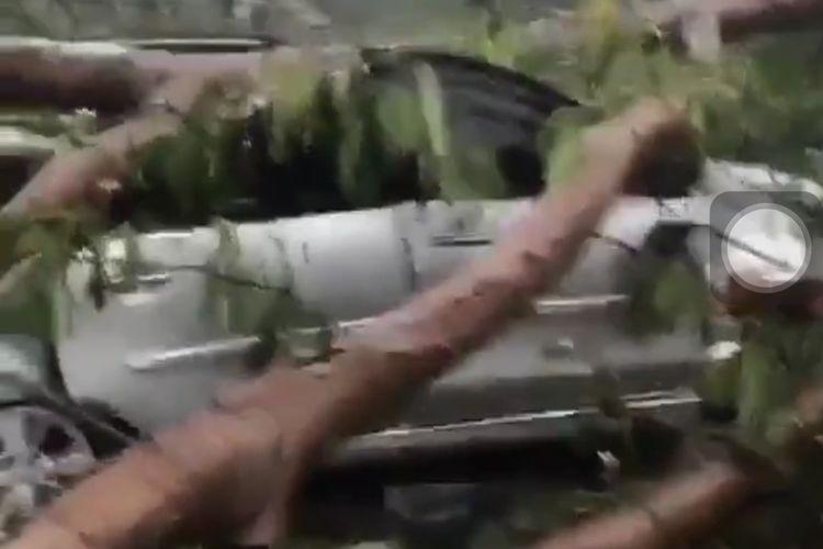 Tangkapan layar akun instagram @info.jakartabarat pohon tumbang menimpa sebuah mobil di kawasan Kembangan, Jakarta Barat, Rabu (14/4/2021).