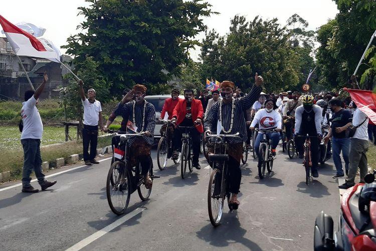 Paslon Wali Kota dan Wakil Wali Kota Solo, Gibran Rakabuming Raka dan Teguh Prakosa memakai pakaian adat Jawa dengan menaiki sepeda onthel menuju ke Kantor Komisi Pemilihan Umum (KPU) Solo, Jawa Tengah, Jumat (4/9/2020).