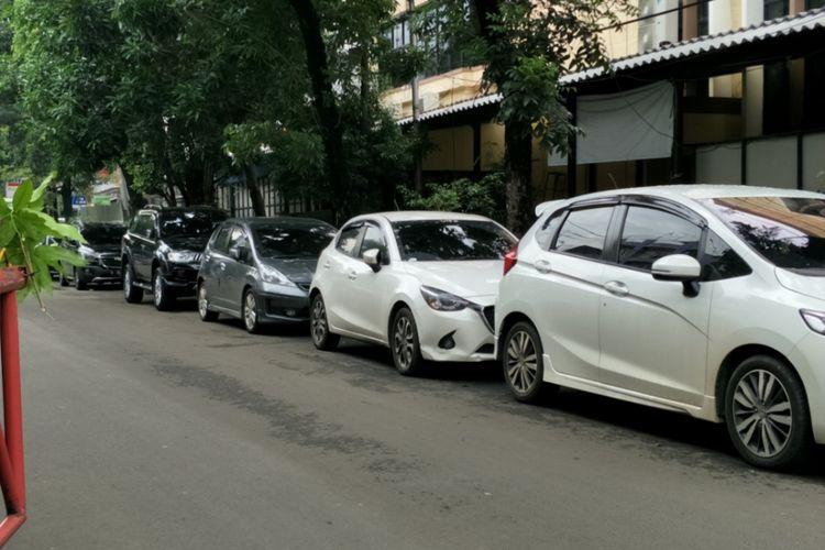 Puluhan mobil pribadi terparkir di badan Jalan Dokter Susilo, Grogol Petamburan, Jakarta Barat, Minggu (19/11/2017).