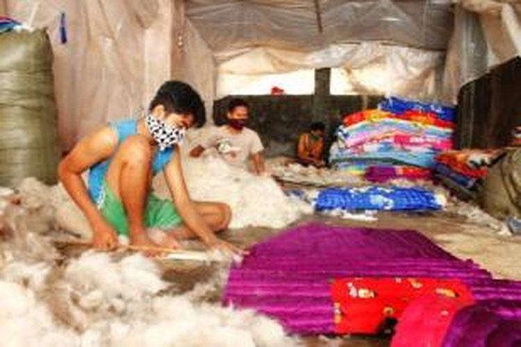 Jaya memasukan kapuk ke dalam kasur lesehan, di Desa Cikeduk, Kecamatan Depok, Kabupaten Cirebon, (24/9/2014). Ia satu dari belasan pria yang berkerja di sentra produksi kapuk.