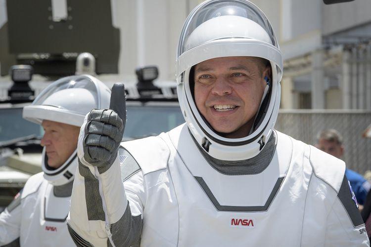 Astronot Robert Behnken (depan) dan Douglas Hurley mengenakan pakaian antariksa SpaceX, saat hendak naik ke pesawat ruang angkasa SpaceX Crew Dragon di Kennedy Space Center di Florida, AS, Jumat (30/5/2020) atau Sabtu (31/5/2020) waktu Indonesia. NASA meluncurkan dua astronotnya ke Stasiun Luar Angkasa Internasional (ISS) pada hari ini, yang merupakan peluncuran pertama astronot ke orbit oleh pihak swasta dan pesawat luar angkasa berawak pertama NASA dari AS dalam 9 tahun terakhir.