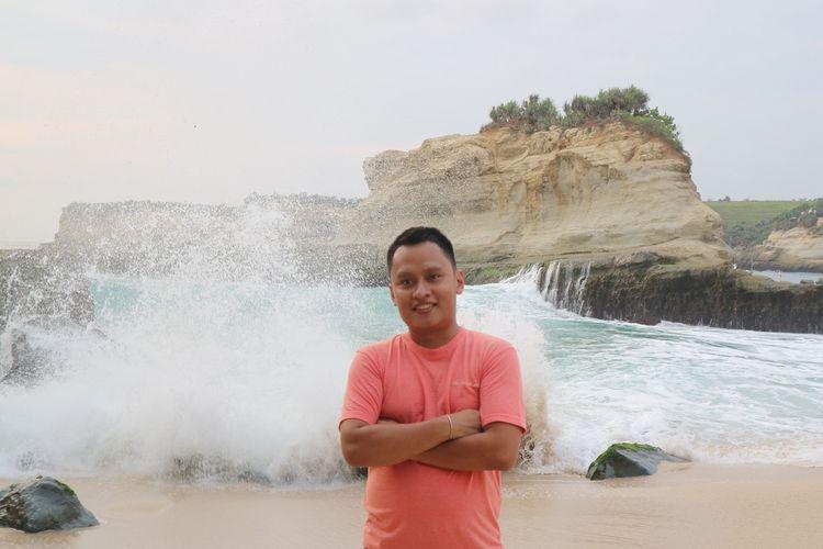 Seorang wisatawan berfoto berlatar belakang ombak Pantai Klayar, Pacitan, Jawa Timur, Selasa (28/1/2020).