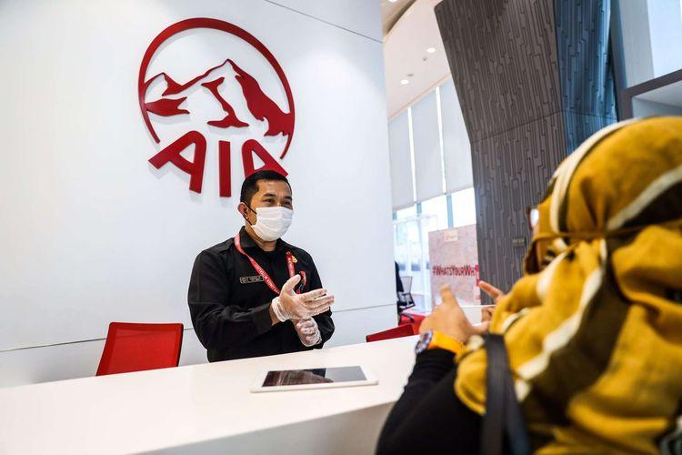 Petugas Customer Service PT AIA FINANCIAL (AIA) menggunakan masker dan pelindung wajah saat melayani nasabah di Customer Service Center, AIA Central, Jakarta Pusat, Rabu (17/6/2020).