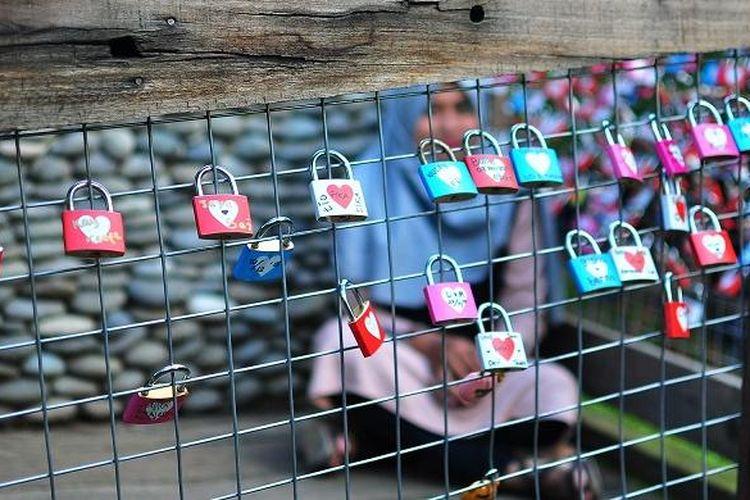 Seorang pengunjung bersembunyi di balik pagar penuh gembok cinta di Farm House Lembang, Selasa (22/12/2015). Lokasi ini bisa jadi salah satu spot foto bagus.