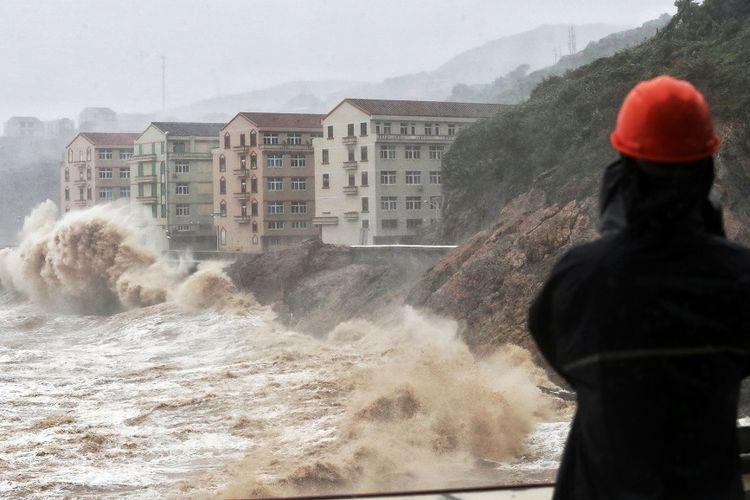 Gelombang tinggi menghantam dinding laut di depan bangunan di Taizhou, provinsi Zhejiang, China timur, yang disebabkan Topan Lekima, pada Jumat (9/8/2019).