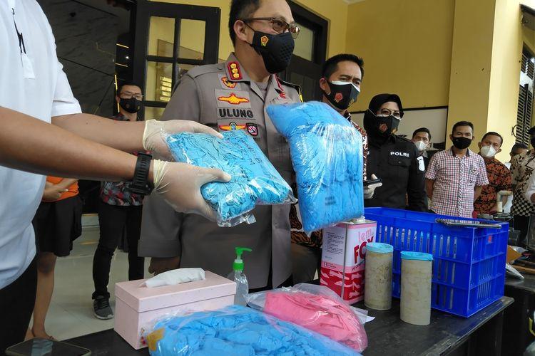 Polrestabes Bandung, Kombes Pol Ulung Sampurna Jaya tengah memperlihatkan barang bukti limbah sarung tangan medis yang direkondisi menjadi baru, Jumat (20/11/2020) di Mapolrestabes Bandung.