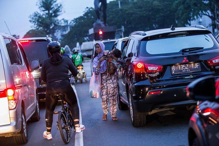 Seorang ibu menggendong anaknya saat menjual tisu di Kawasan Senayan, Jakarta Selatan, Sabtu (3/10/2020). Pembatasan sosial berskala besar (PSBB) di Jakarta untuk mengendalikan penularan Covid-19 telah memasuki pekan ketiga.