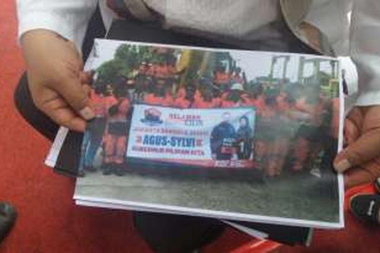 Sebuah foto yang menunjukan pasukan oranye Dinas Kebersihan DKI berfoto dengan membawa spanduk Agus Yudhoyono dan Sylviana Murni. Foto ini menjadi bukti ketidaknetralan pasukan oranye. Mereka diberi sanksi skors hingga masa kontrak habis.