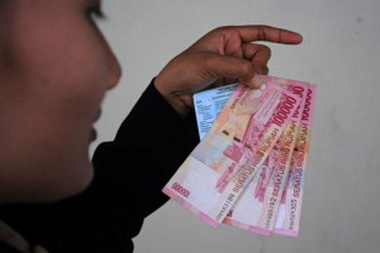 Warga di Pamekasan menunjukkan uang dari BLSM. Di Pamekasan ada jemaah calon haji yang kebagian BLSM, namun banyak orang miskin yang luput dari sasaran.
