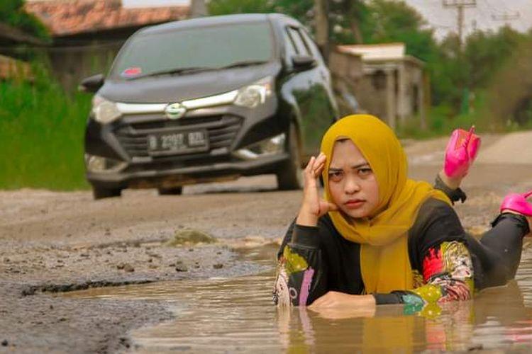 Foto Ummu Hani di Facebook bergaya bak model di kubangan jalan. Aksinya menuai pujian bentuk kritikan tanpa menyakiti ke pemda