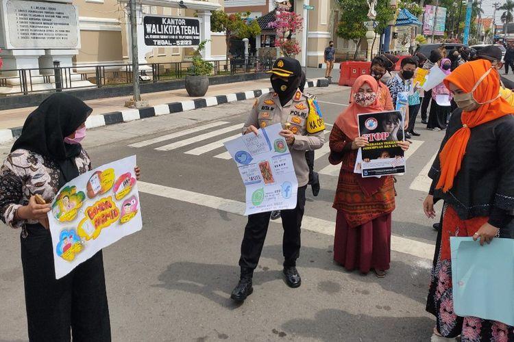 Kapolres Tegal Kota AKBP Rita Wulandari bersama anak dan perempuan lainnya saat mengampanyekan perlindungan dan pemenuhan hak dalam peringatan Hari Anak Nasional, di Alun-alun Kota Tegal, Kamis (23/7/2020)