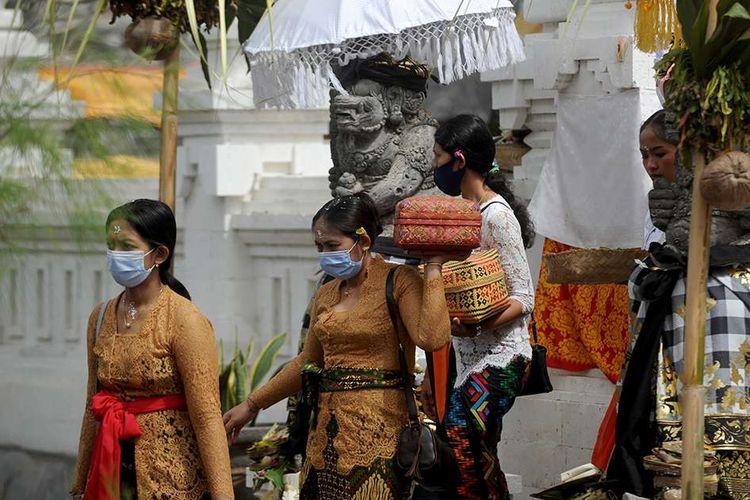 Warga membawa sejumlah sesaji saat perayaan Hari Raya Kuningan di Pura Sakenan di Pulau Serangan, Bali, Sabtu (26/9/2020). Hari Raya Kuningan yang digelar beberapa hari setelah Galungan ini dimaksudkan untuk merayakan saat Dewa-dewa dan leluhur kembali ke surga setelah bertemu keturunannya.
