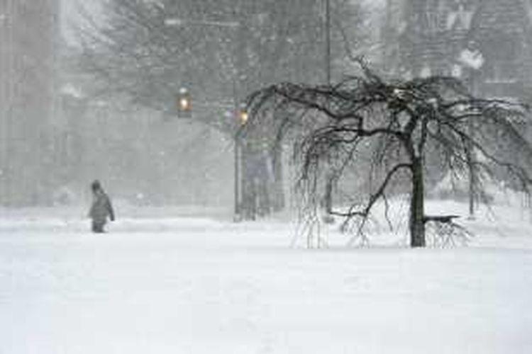 Seorang pria melintasi kawasan Thomas Circle di Washington DC, yang diselimuti salju tebal, Minggu (24/1/2016).