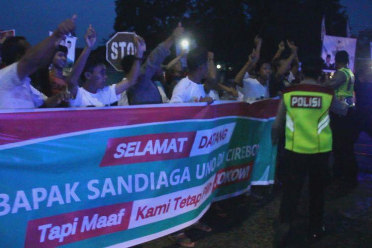"""Sejumlah warga di Desa Mertapada, Kecamatan Astana Japura, Kabupaten Cirebon membentangkan spanduk bertuliskan """"Selamat Datang Bapak Sandiaga Uno Di Cirebon, Tapi Maaf Kami Tetap Pilih Jokowi"""", Jumat petang (1/3/2019). Tak hanya membentangkan spanduk, para warga ini juga berulang kali meneriakan kata Jokowi ke arah Sandi. Sandi menilai itu realitas demokrasi."""