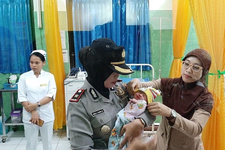 Kapolsek Ngemplak Kompol Wiwik Haritulasmi saat mengendong bayi di Puskesmas Ngemplak I.