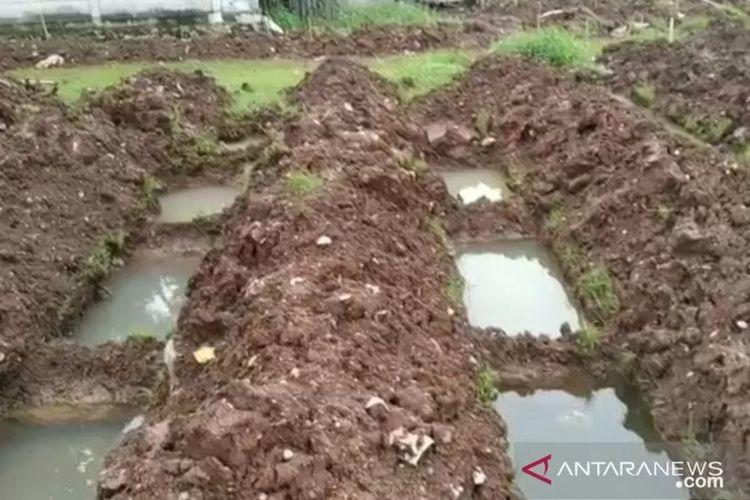 Liang lahat siap pakai di TPU Bambu Apus, Jakarta Timur, terisi oleh genangan air hujan akibat kontur lahan yang miring serta intensitas curah hujan yang lebat, Kamis (18/2/2021).