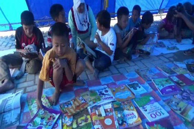 Sejak dua pekan tak sekolah karena gempa, relawan literasi Mamasa sulawesi barat menyediakan beragam buku bacaan di tenda pengungsian korban gempa Mamasa