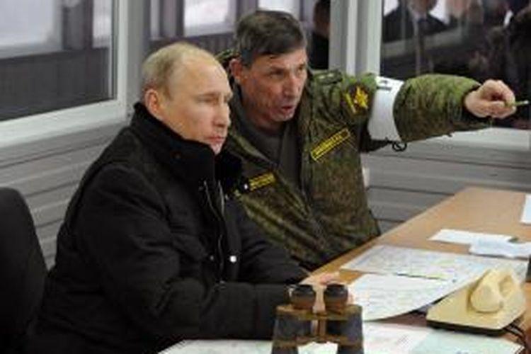 Presiden Rusia Vladimir Putin mendengarkan penjelasan Komandan Persiapan Tempur Angkatan Darat Rusia, Ivan Buvaltsev saat meninjau latihan militer di Kirillovsky, kawasan Leningrad, Senin (3/3/2014).