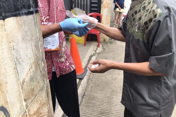 Penggunaan sarung tangan plastik di TPS 015 di Jalan Mani Nomin  No 7 RT 03/04, Kelurahan Kukusan, Beji, Kota Depok, Jawa Barat pada Rabu (9/12/2020).