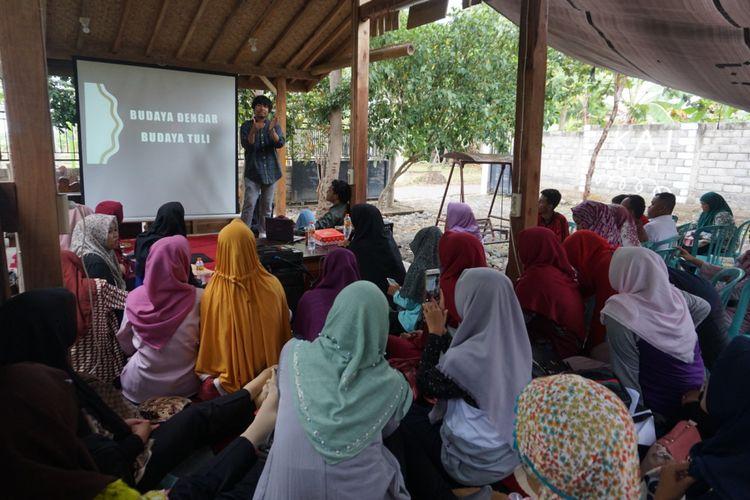 Seorang anggota Akar Tuli sedang mengajarkan Bisindo kepada ibu dan juga guru di salah satu cafe di Banyuwangi Jumat (9/11/2018)