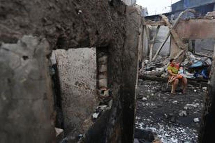 Warga korban kebakaran di Tambora, Jakarta Barat, duduk di kawasan rumahnya yang telah hangus, Minggu (27/9/2015).