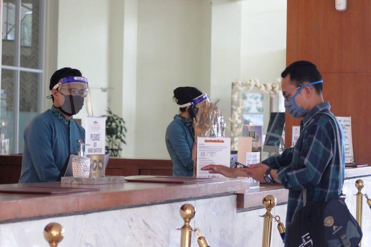 Seorang tamu hotel di Puncak, Cianjur, Jawa Barat, saat melakukan reservasi di lobi hotel di tengah era new normal.