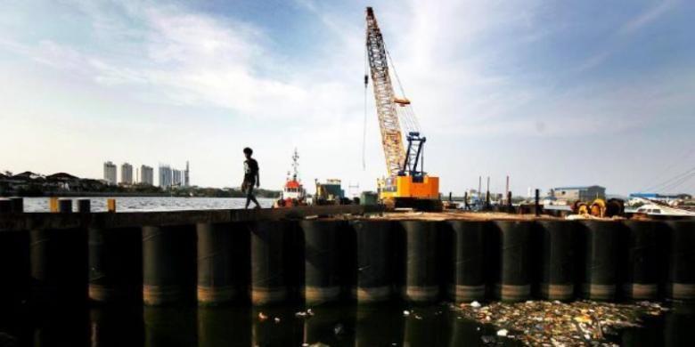 Warga melintas di antara dinding tabung raksasa yang dipasang sebagai bagian dari proyek pembangunan tanggul laut raksasa di Jakarta Utara, November 2014.