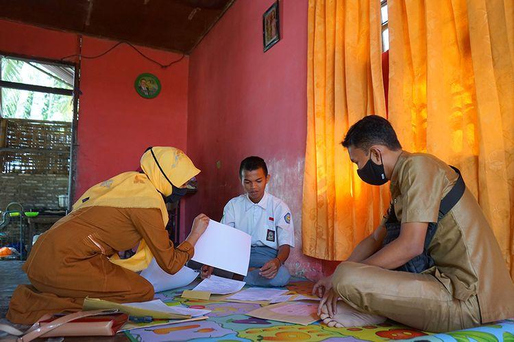 Dua guru SMA Negeri 1 Kabila mengawasi siswa yang melakukan ujian semester secara luar jaringan (luring) di rumah di Poowo, Kabupaten Bone Bolango, Gorontalo, Selasa (9/6/2020). Sejumlah guru di sekolah tersebut mengantarkan soal ujian ke rumah 51 siswa karena tidak memiliki telepon pintar (smart phone) untuk mengikuti ujian dalam jaringan (daring).