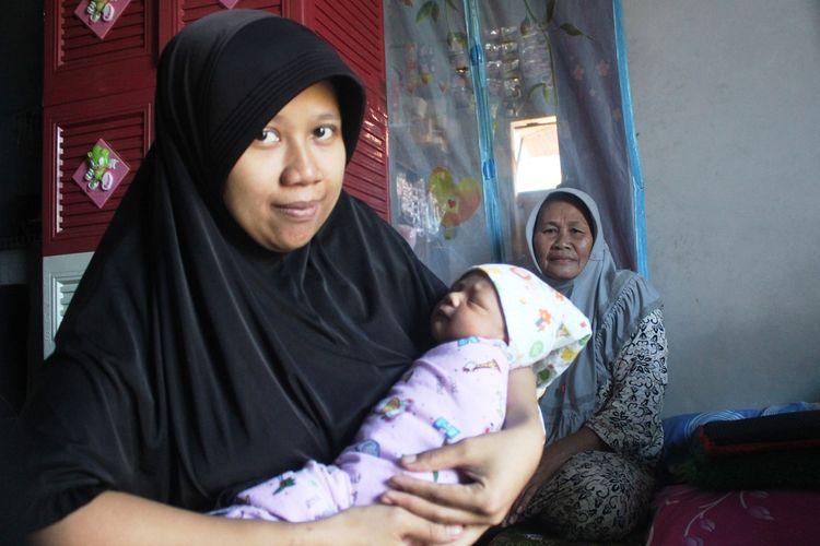 Riska (27), menggendong bayinya, yang baru berumur sepekan di rumahnya di Desa Rahong, Cianjur, Jawa Barat, Jumat (17/01/2020). Riska membayar biaya persalinan anak pertamanya itu menggunakan uang koin pecahan Rp1..000.