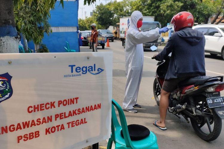 Petugas paramedis memeriksa suhu tubuh menggunakan thermo gun bagi warga yang melintasi posko check point di Jalan Proklamasi, Kota Tegal, Jawa Tengah saat pelaksanaan PSBB, Kamis (7/5/2020)