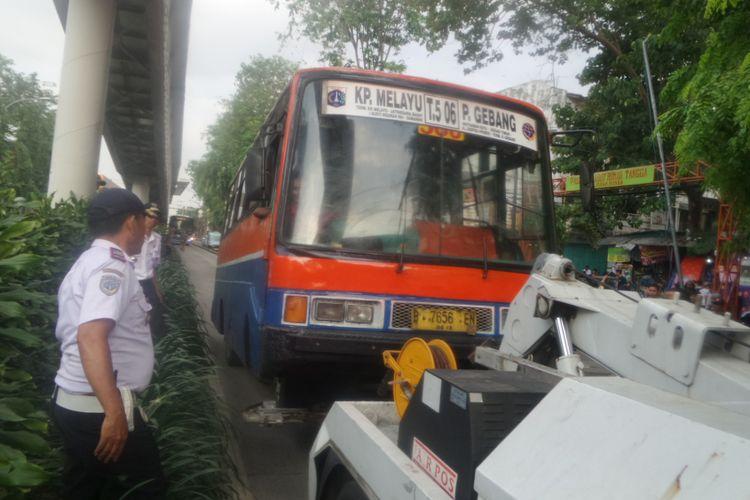 Petugas dari Suku Dinas Perhubungan Jakarta Timur menderek sebuah metromini jurusan Kampung Melayu-Pulogebang yang melintas di jalur busway di Jalan Bekasi Barat, Jakarta Timur. Sopir tersebut marah-marah karena tak terima bus yang dia kendarai diderek petugas, Rabu  (2/8/2017)