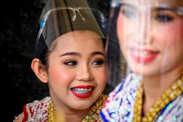 Penari tradisional Thailand yang mengenakan pelindung wajah tampil di Kuil Erawan, yang dibuka kembali setelah pemerintah Thailand melonggarkan langkah-langkah untuk memerangi penyebaran coronavirus novel COVID-19, di Bangkok pada 4 Mei 2020. Thailand mulai melonggarkan pembatasan terkait dengan COVID -19 pada 3 Mei dengan memungkinkan berbagai bisnis untuk dibuka kembali, tetapi memperingatkan bahwa langkah-langkah yang lebih ketat akan diberlakukan kembali jika kasus meningkat lagi.