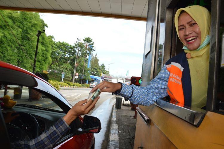 Petugas gardu Jasa Marga sedang melayani pengemudi untuk membayar tol.