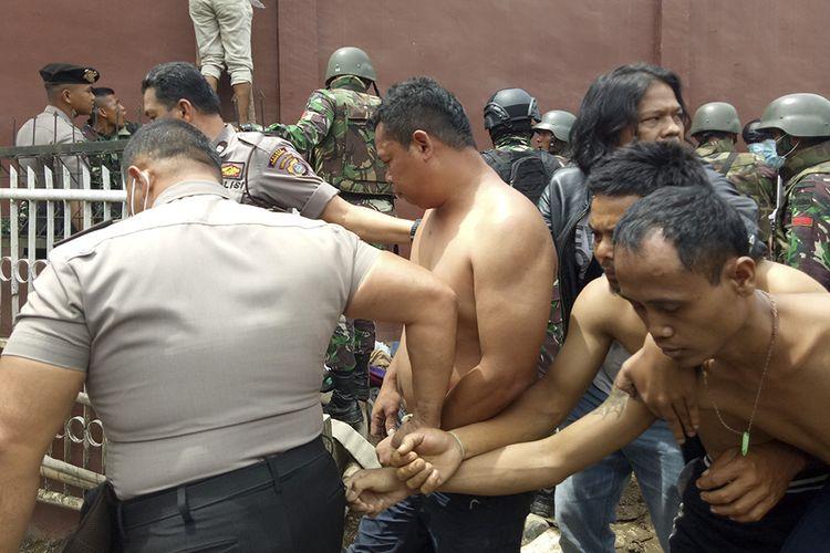 Petugas gabungan menggiring narapidana pascakerusuhan di Rumah Tahanan Negara (Rutan) Kelas II B Kabanjahe, Kabupaten Karo, Sumatera Utara, Rabu (12/2/2020). Menurut Kepala Bagian Humas Ditjen Pemasyarakatan Rika Aprianti, pemicu kerusuhan yang terjadi di rutan tersebut disebabkan adanya warga binaan pemasyarakatan yang tidak terima atas upaya pemberantasan narkoba di dalam rutan.