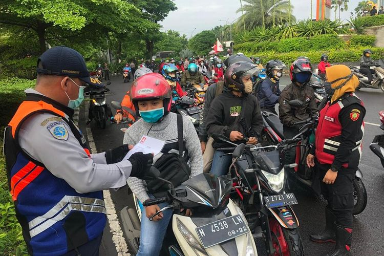 Hari kedua pembatasan sosial berskala besar (PSBB) di Surabaya, arus lalu lintas di perbatasan Surabaya dan Sidoarjo, Jawa Timur, tepatnya di Bundaran Waru, terpantau lancar, Rabu (29/4/2020). Meski kendaraan terlihat padat, arus lalu lintas terpantau lancar.
