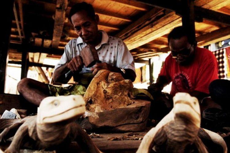 Abdurahman (52, kiri), bersama rekannya menyelesaikan pembuatan patung Komodo di Desa Komodo, Kecamatan Komdo, Manggarai Barat, NTT, Selasa ( 15/12). Mata pencaharian penduduk Desa Komodo adalah nelayan dan pembuat kerajinan patung Komodo, yang pemasarannya bergantung pada pengunjung Pulau Komodo baik warga asing maupun domestik.