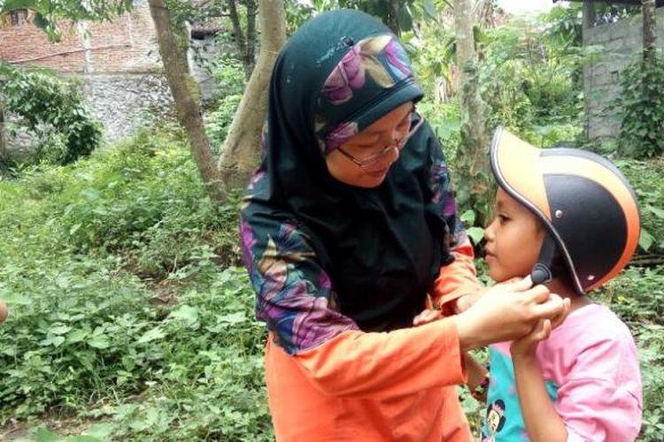 Seorang ibu saat mengenakan helm kepada putrinya sebelum menunggang kuda untuk menyusuri sungai di Sleman, DI Yogyakarta.