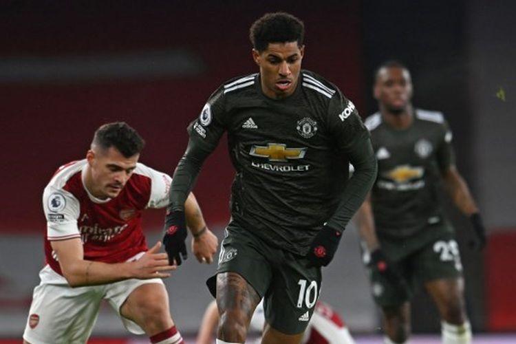 Penyerang Manchester United, Marcus Rashford, menjauh dari kejaran gelandang Arsenal Granit Xhaka dalam laga Premier League 2020-2021 di Stadion Emirates, 30 Januari 2021.