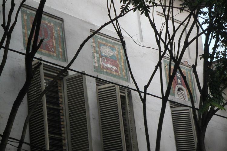 Simbol kota dengan seni patri kaca, diantaranya simbol Kota Surabaya dengan gambar ikan hiu dan buaya, terdapat di bagian dinding luar gedung bekas Escomptobank (dibangun tahun 1904) yang menghadap Jalan Pintu Besar Utara, Jaka rta .
