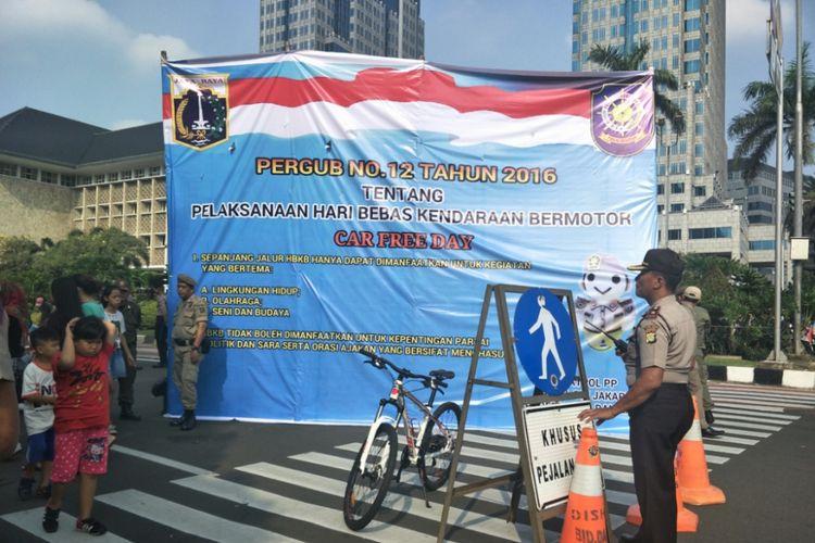 Satpol PP DKI Jakarta memasang banner berisikan larangan pelaksanaan kegiatan partai digelar di kawasan Car Free Day (CFD) atau hari bebas kendaraan bermotor (HBKB), Minggu (6/5/2018).