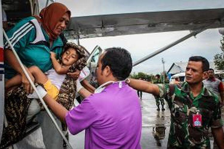 Anggota SAR membantu menurunkan seorang anak korban gempa 6,2 Skala Richter dari pesawat di Banda Aceh, Rabu (3/7/2013).
