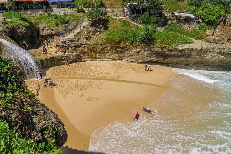 Pantai Banyu Tibo di Pacitan dengan air terjun yang langsung mengarah ke pantai.