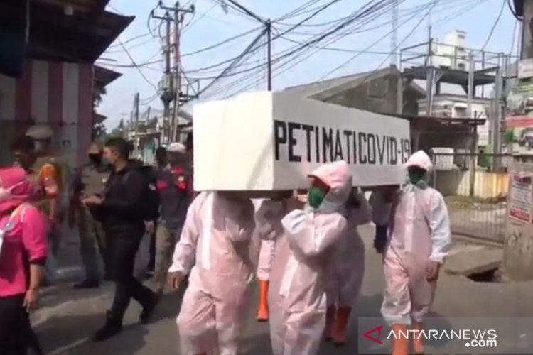 Petugas gabungan di Kecamatan Cakung, Jakarta Timur, berkeliling perkampungan padat hunian dengan mengarak peti jenazah COVID-19 dalam rangka penertiban protokol kesehatan, Selasa (8/9/2020).