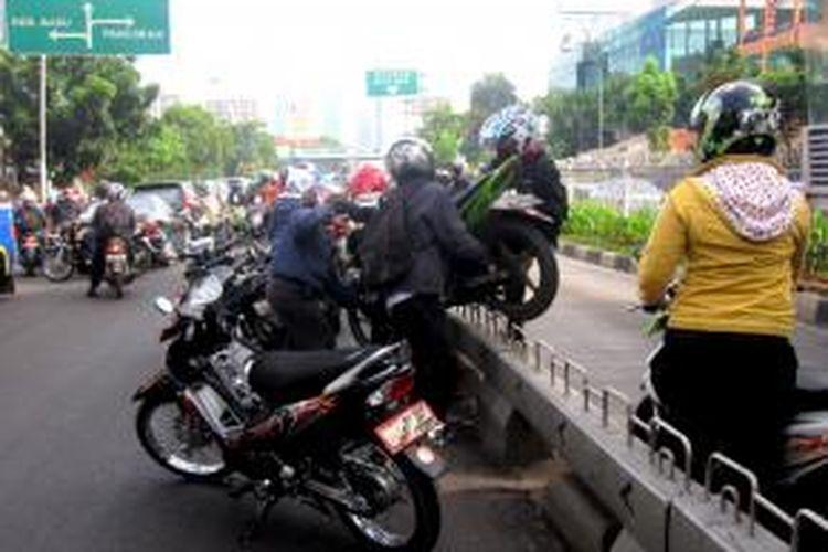 Pengendara motor di jalur transjakarta saling bahu membahu mengangkat motor yang terancam ditilang oleh polisi di kawasan Mampang, Jakarta Selatan, Kamis (21/11/2013).